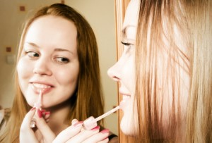 Woman applying makeup in front of a mirror.